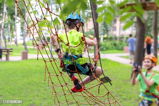 istock Little boy in safety equipment climbing on rope wall at adventure park. Fiend making a photo shot on smartphone. Children summer sport extreme outdoor activity. Back view 1137638284
