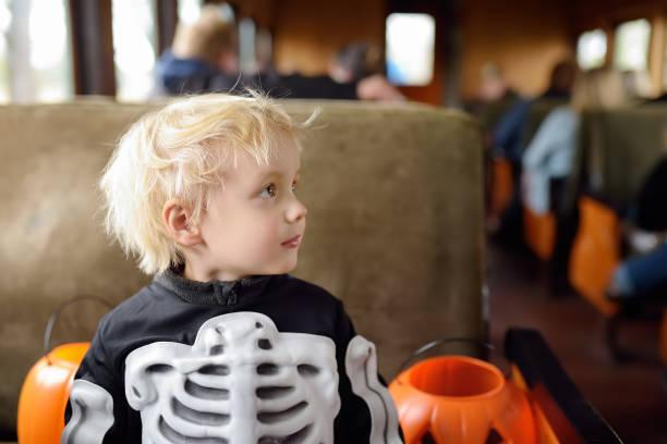 kleiner junge in beängstigend kostüm skelett fahrt in traditionellen zug express auf feiern halloween - festzugskleidung stock-fotos und bilder