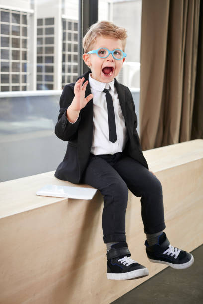 Little boy in spectacles and suit stock photo