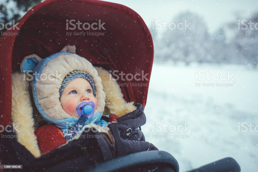 Little boy in stroller in winter park stock photo