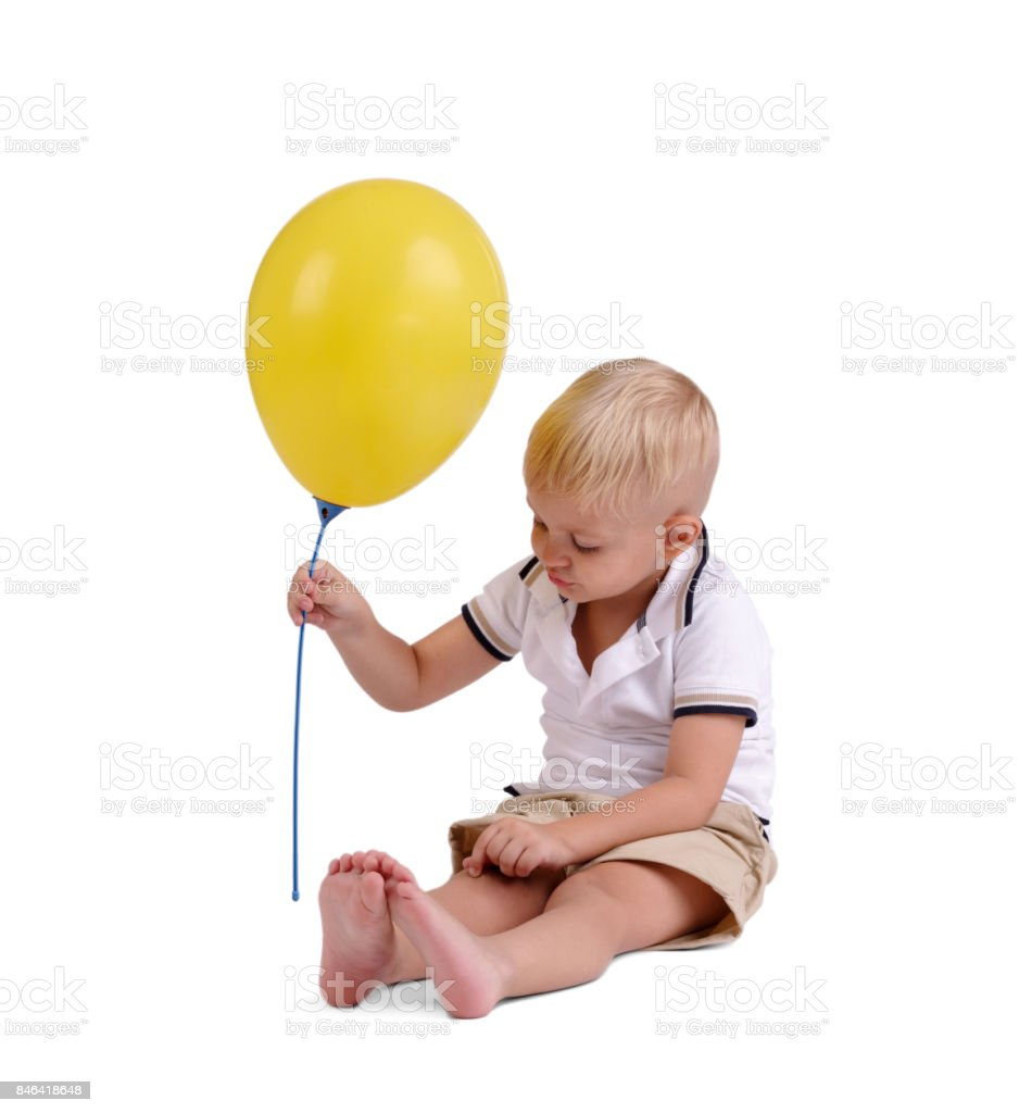 Little boy in summer clothes playing with balloon sitting on the floor. Happiness. Birthday party. stock photo