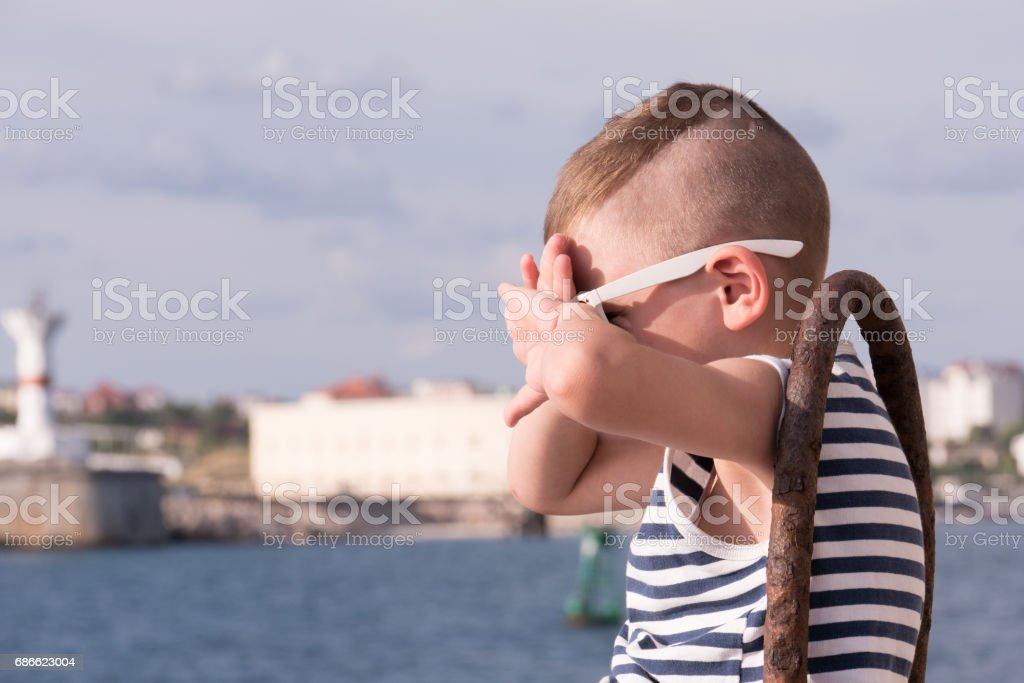 Little boy in sunglasses covers his face from the sun royalty-free stock photo