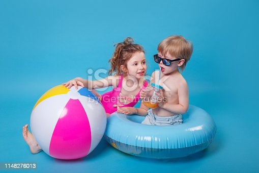istock Little boy in sunglasses with inflatable ring toy and girl with big inflatable ball on blue background 1148276013