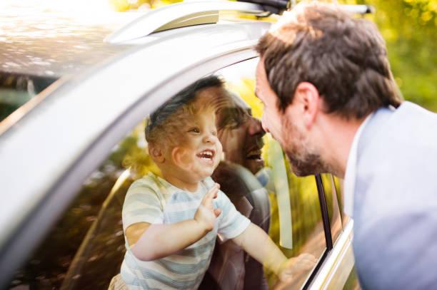 petit garçon dans la voiture en regardant son père. - homme faire coucou voiture photos et images de collection