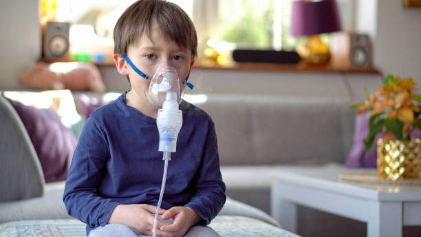 Little boy in the inhalation mask with breathing troubles stock photo