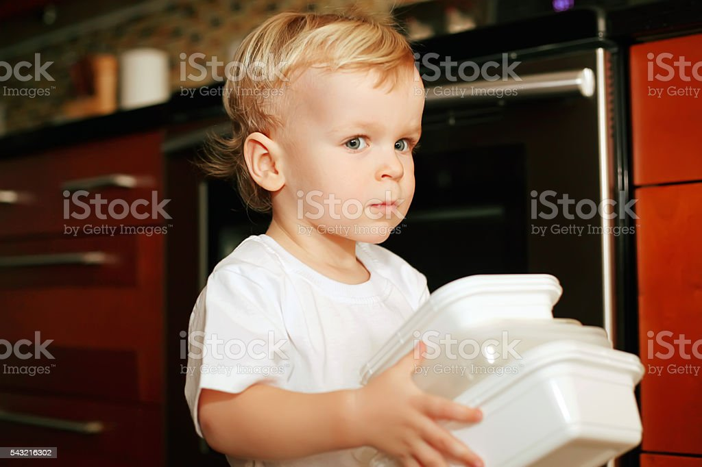 Little boy in the kitchen carrying plastic containers stock photo