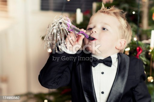 Little boy makes some noise with a party horn blower. He is wearing a tuxedo. Shallow depth of field. Focus on the horn blower.