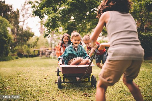 Smiling and laughing little boy sitting in a red wagon which is being pushed at the back and pulled at the front by his friends over grass in a sunny park