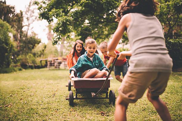 Petit garçon étant poussé et chariot tiré par des amis - Photo