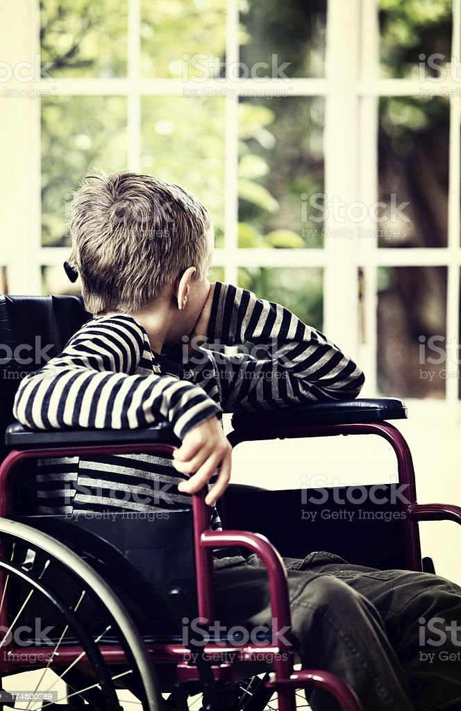 Little boy in wheelchair looks out at unreachable garden wistfully stock photo
