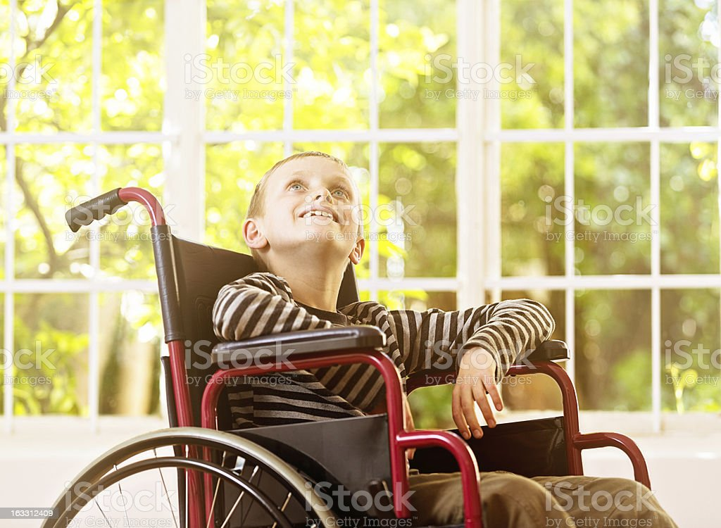 Little boy in wheelchair looks up, smiling, ever hopeful stock photo