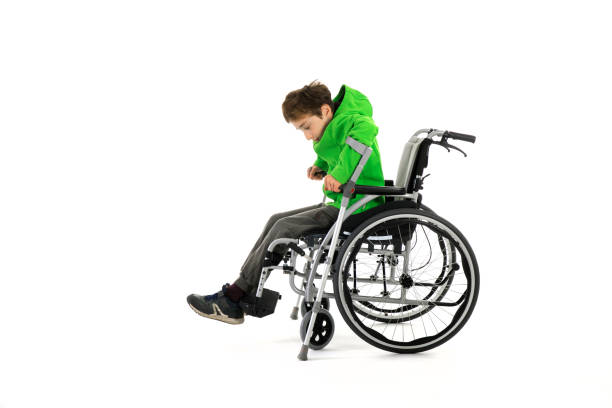 Little boy in wheelchair on white background. Wheelchair user gets up, moves away from the wheelchair. Young male person got up from a wheelchair as a result of rehabilitation – zdjęcie
