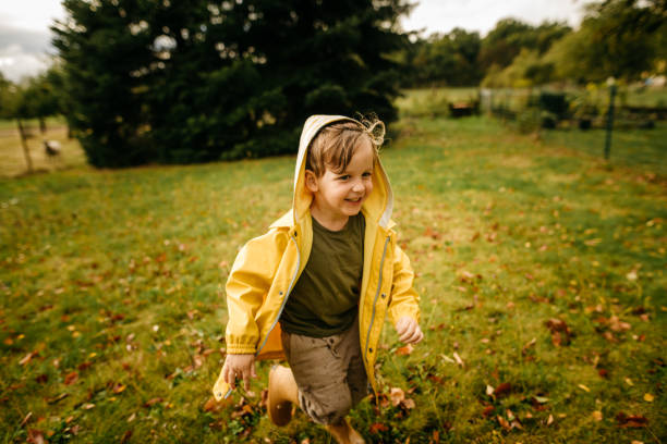 Little boy in yellow raincoat running outside stock photo