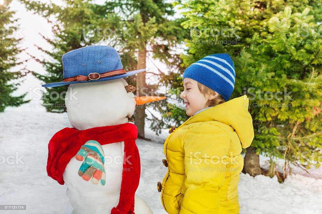 Little boy in yellow with beautiful snowman stock photo