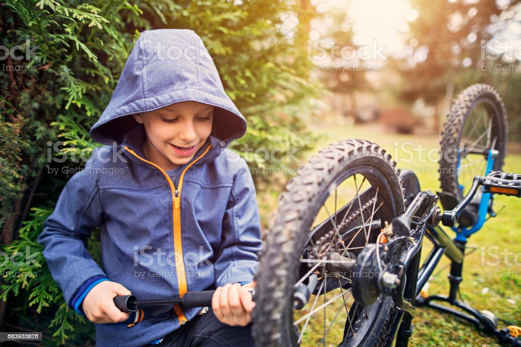 Little boy inflatingf bicycle tires stock photo
