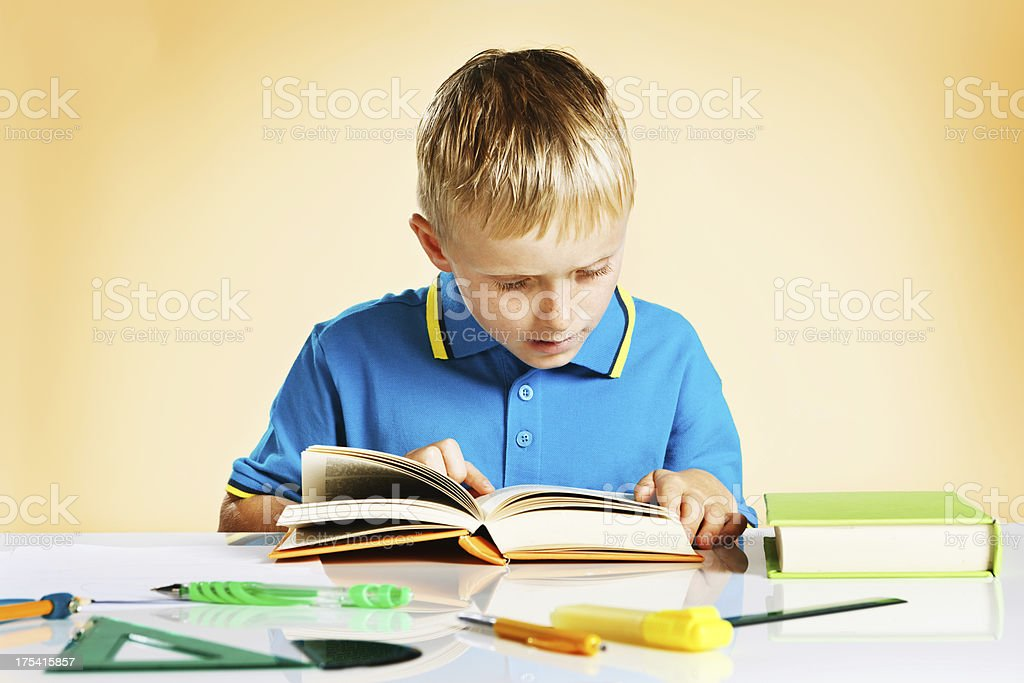 Little boy intent on reading book at school desk stock photo
