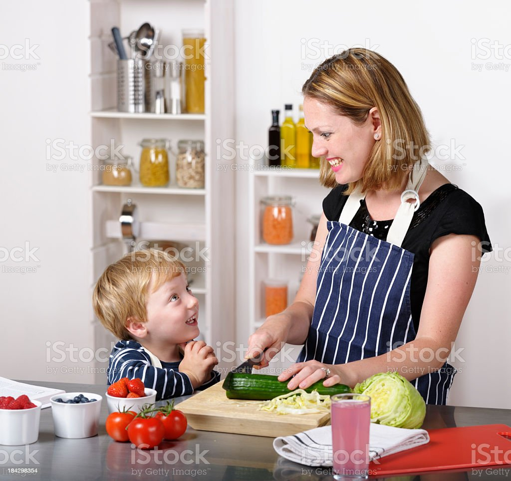 Little Boy Interacting With His Mother While She Preapres Meal royalty-free stock photo