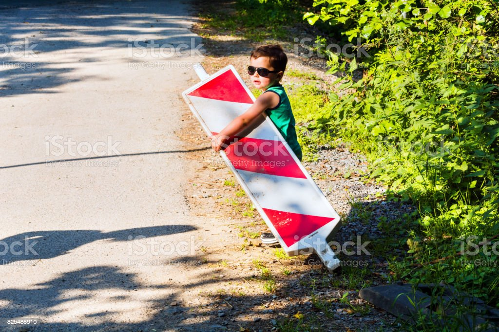 Little boy is carrying a construction site barrier stock photo