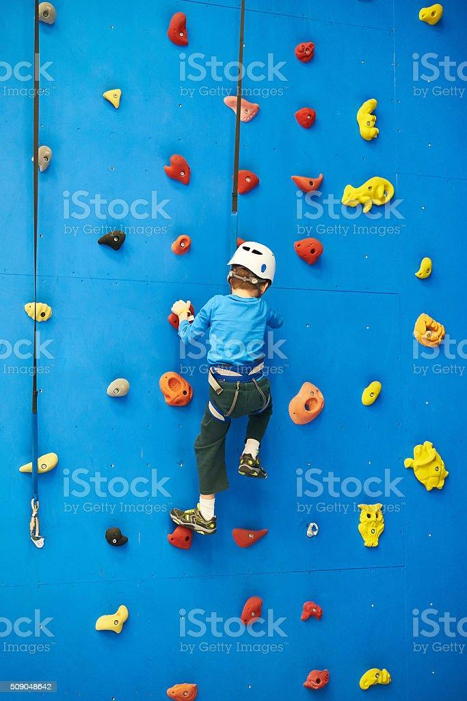 Little boy is climbing on blue wall stock photo
