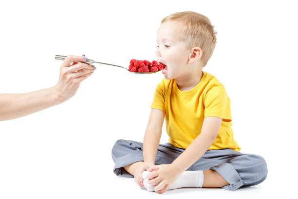 Little boy is eating raspberries, isolated over white stock photo