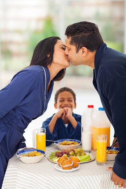 ragazzino è ridere quando vedere i genitori baciare la prima colazione - kids kiss embarrassed foto e immagini stock