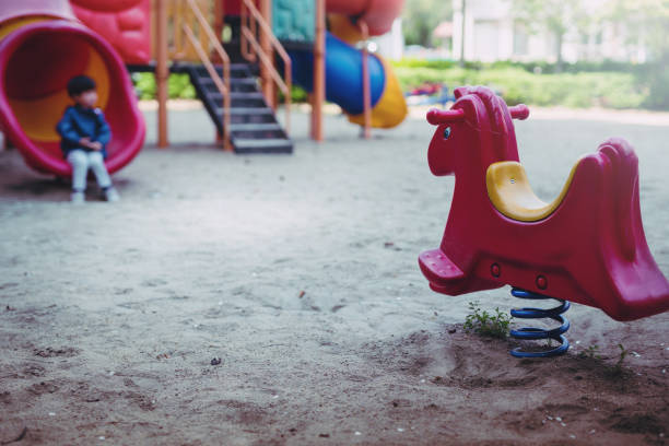 little boy is playing lonely in playground. little boy is sitting unhappy in playground. - criança perdida imagens e fotografias de stock