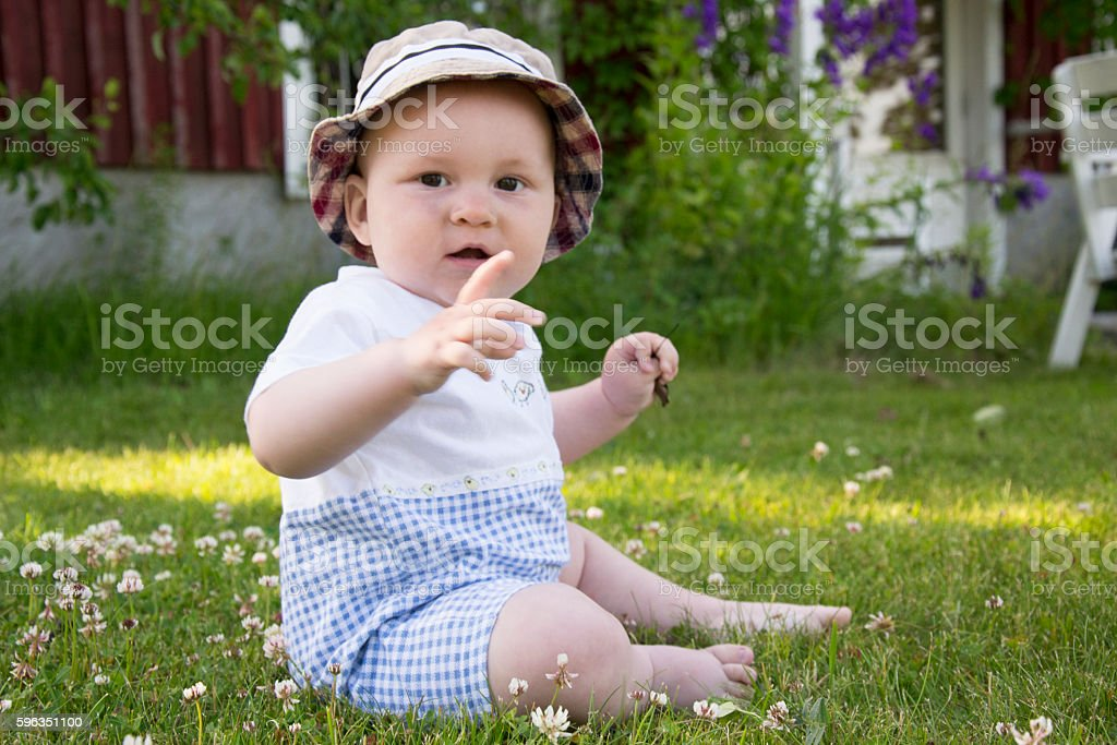 Little boy is playing on grass among flowers royalty-free stock photo
