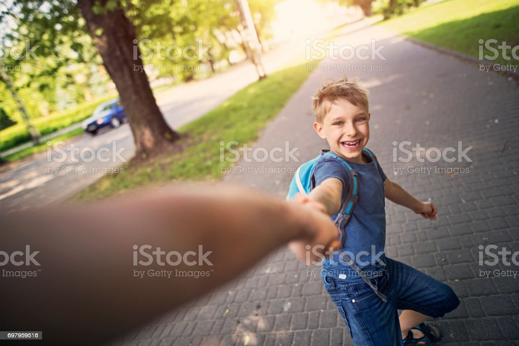 Little boy is pulling his father to city park. stock photo