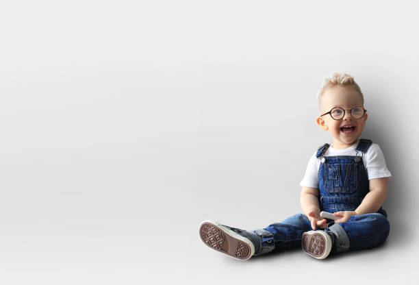 Little boy is smiling Little boy in denim overalls is smiling bib overalls boy stock pictures, royalty-free photos & images