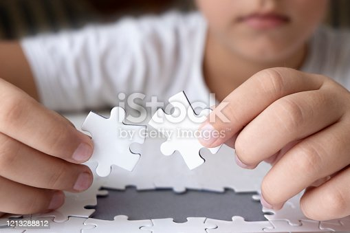 514261930 istock photo Little boy is trying to connect jigsaw puzzle pieces. 1213288812