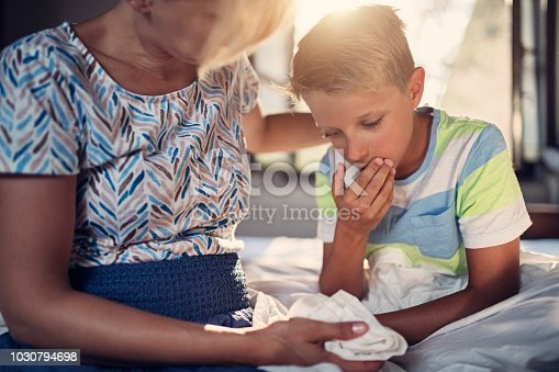 Sick little boy sitting on bed. The boy is coughing, feeling sick and nauseous. The comforting the boy. Nikon D850