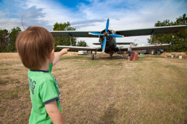 Little boy is watching on an airplane with big propeller stock photo