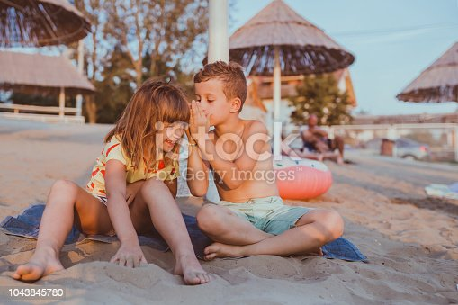 Little boy is whispering a secret into girl ear while playing on a sandy beach