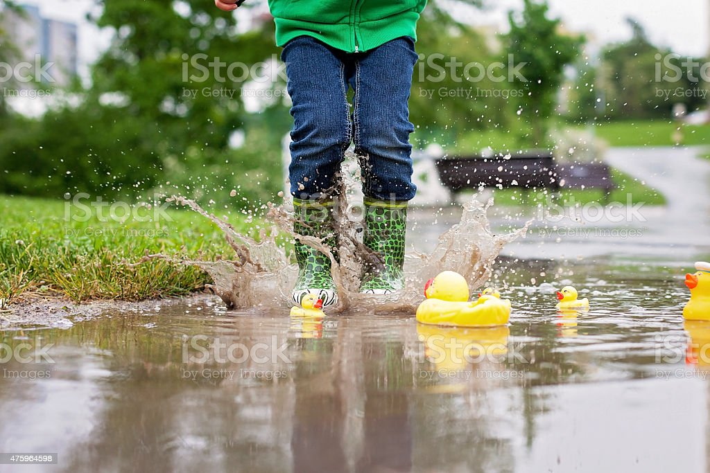 Little boy, jumping in muddy puddles in the park stock photo