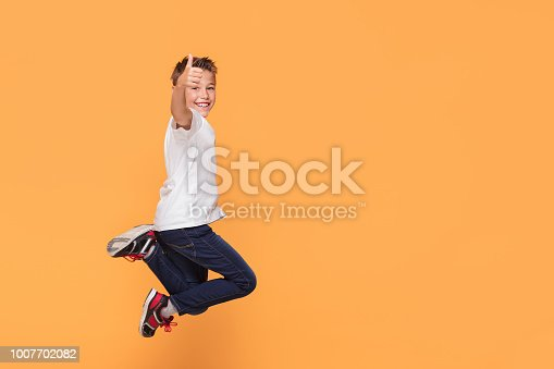Little school boy jumping in the studio on a yellow background. Concept of happy childhood.