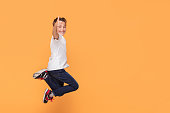istock Little boy jumping in the studio, smiling. 1007702082
