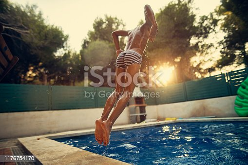 Little boy aged 10 jumping into swimming pool. The boy is caught mid air.   Summer day sunset in Majorca, Spain. Nikon D850
