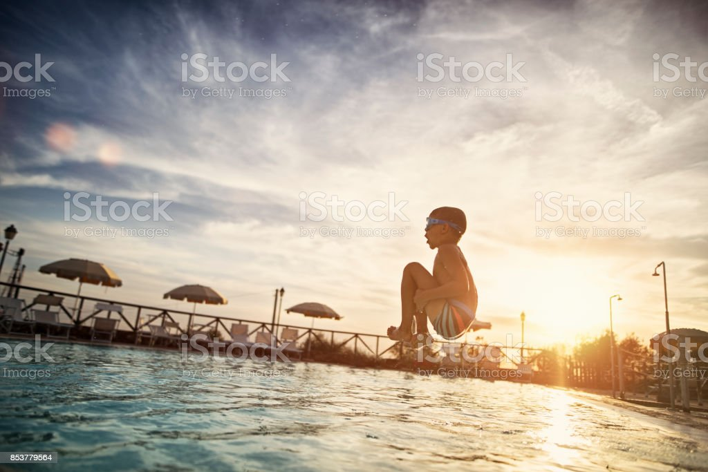 Little boy jumping into swimming pool stock photo