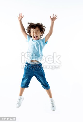 istock Little boy jumping isolated on white background 614845216