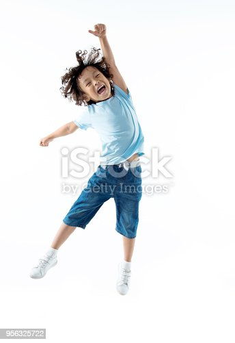 istock Little boy jumping isolated on white background 956325722
