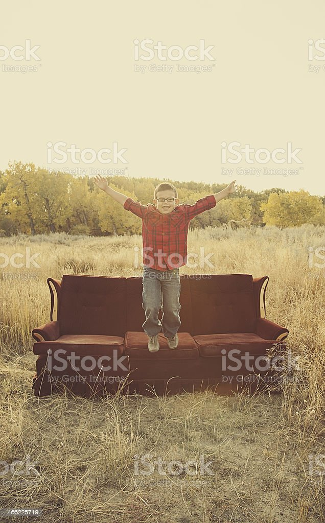 Little Boy Jumping off a Couch royalty-free stock photo
