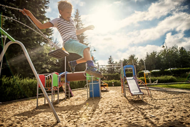 Little boy jumping off the swing stock photo