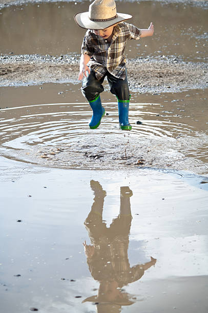 little boy jumping through mud puddle - kellyjhall stock pictures, royalty-free photos & images