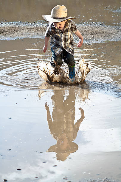 Little boy jumping through mud puddle stock photo