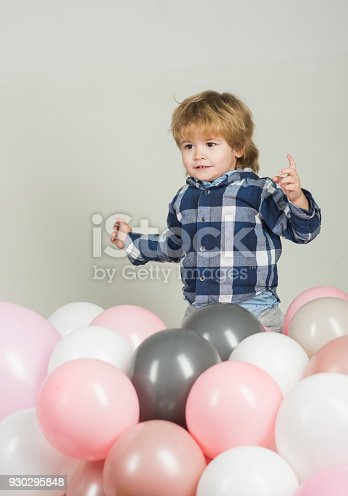 istock Little boy jumps in pink balloons. Funny kid play on his own on white background. Pink, white and gray balloons for celebration. Cute boy wearing blue shirt and grey jeans. Clothes for children 930295848