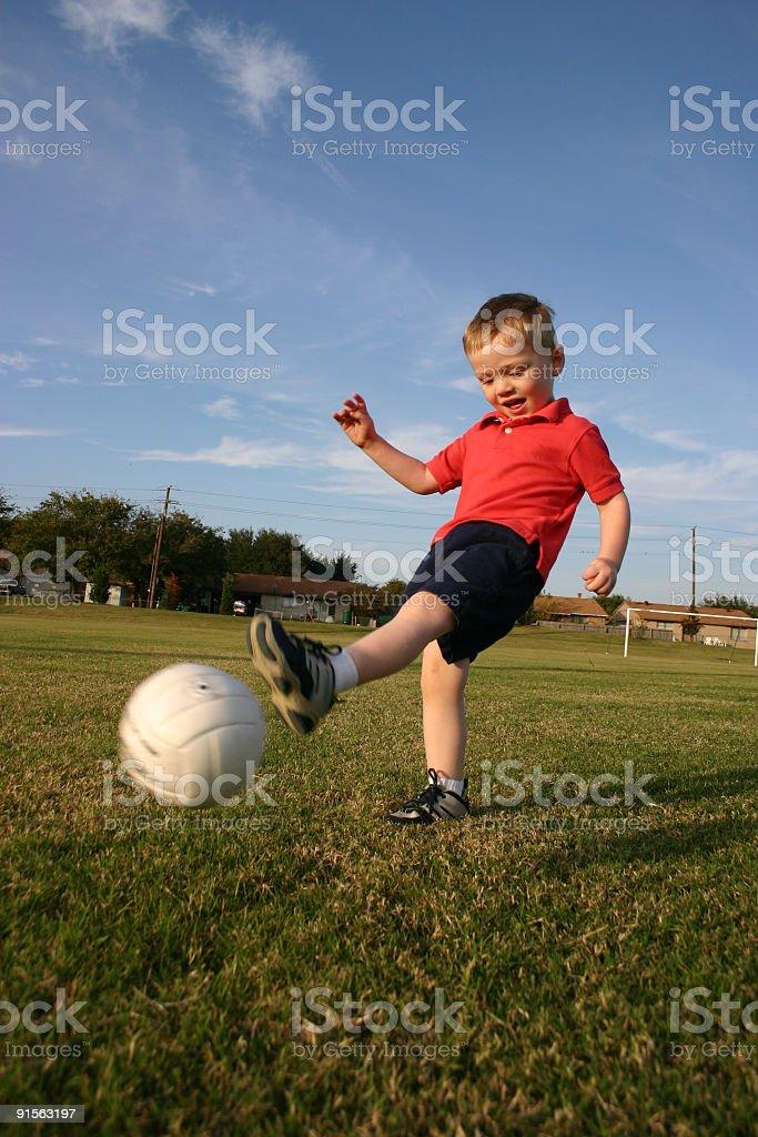 Little boy kicking a white ball stock photo