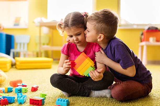 little boy kissing girl who is playing with toy blocks. - little girls little boys kissing love stock photos and pictures
