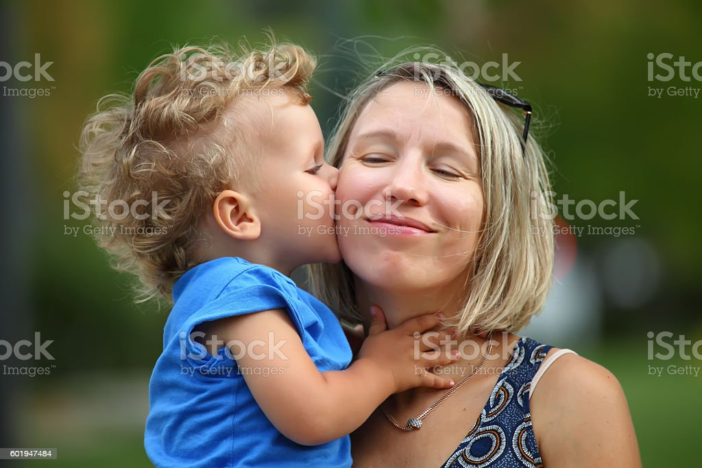 Little boy kissing his mother stock photo