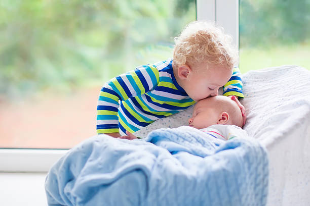 Little boy kissing newborn baby brother Cute little boy kissing his newborn brother. Toddler kid meeting new born sibling. Infant sleeping in white bouncer under a blanket. Kids playing and bonding. Children with small age difference. brother stock pictures, royalty-free photos & images