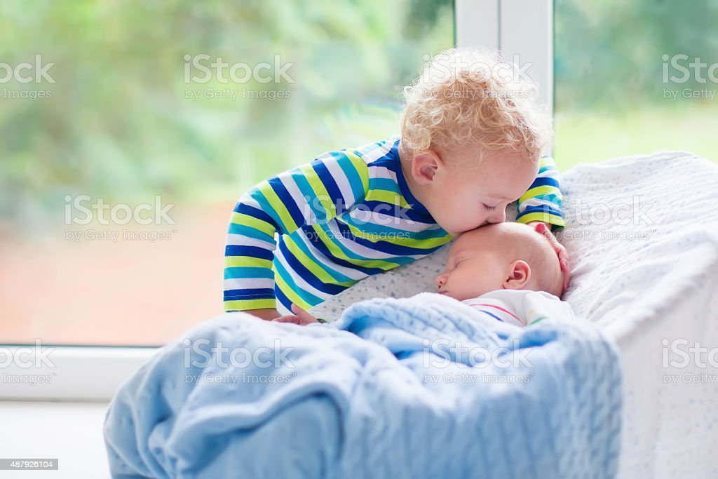 Little boy kissing newborn baby brother stock photo